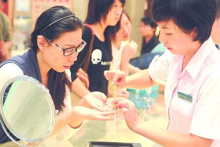 商场的工作人员在为顾客介绍黄金饰品 新华社 图
