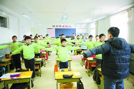 北京,小学学生在教室内做形体操。