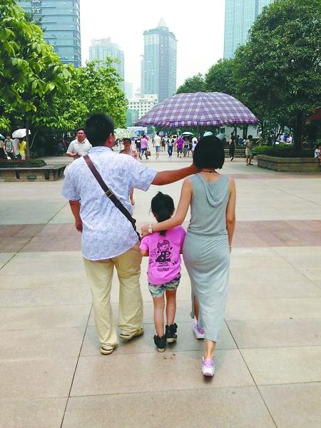 男子撑伞为妻子和女儿遮阴