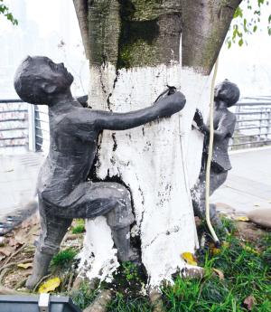 几个小孩雕塑抱着树干